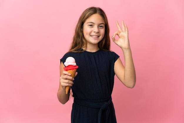 Enfant avec une glace au cornet sur fond rose isolé montrant un signe ok avec les doigts