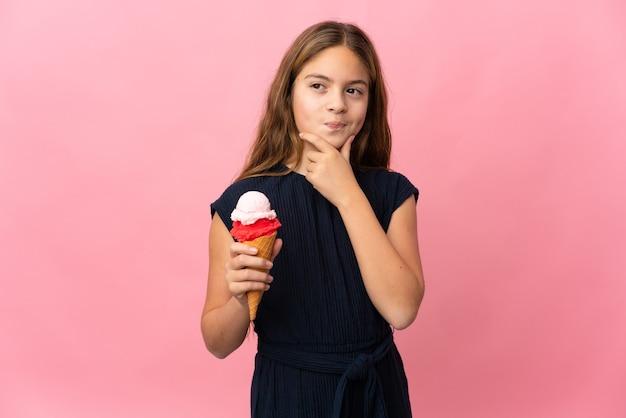 Enfant avec une glace au cornet sur rose isolé ayant des doutes