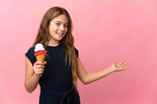 Enfant avec une glace cornet sur fond rose isolé étendant les mains sur le côté pour inviter à venir