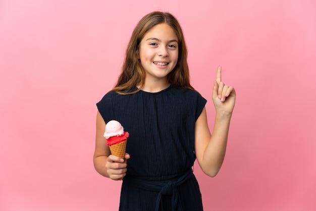 Enfant avec une glace cornet sur fond rose isolé montrant et en soulevant un doigt en signe de la meilleure