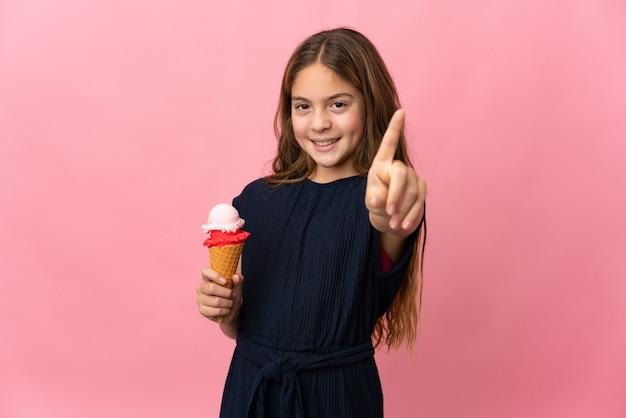 Enfant avec une glace cornet sur fond rose isolé montrant et en soulevant un doigt