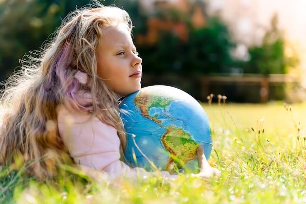 Enfant avec globe terrestre portrait d'une fille européenne blonde de l'école primaire avec un g...