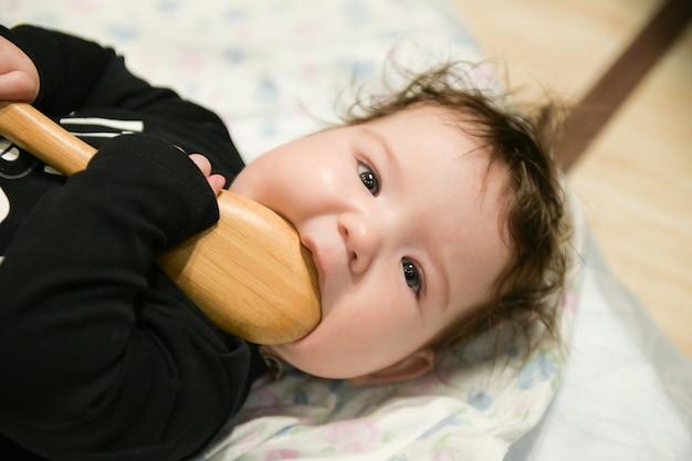 L'enfant grignote une cuillère en bois. nouveau-né grignote une cuillère en bois sur le lit. démangeaisons des dents