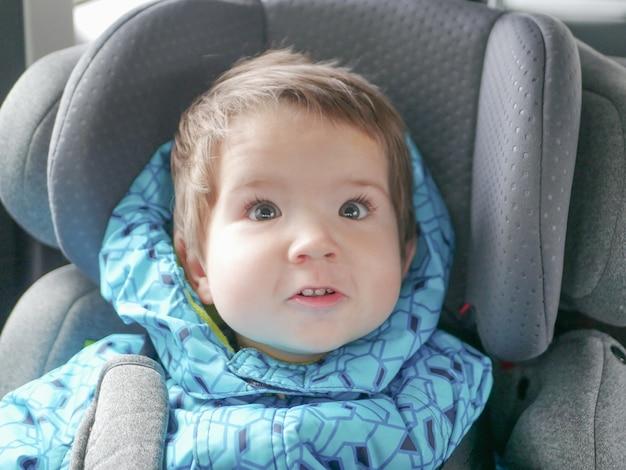 Enfant grimaçant dans un siège d'auto. sécurité des enfants dans le siège auto de l'enfant pendant le sommeil.