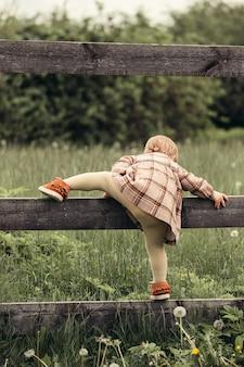 Enfant grimpe sur une clôture dans le jardin