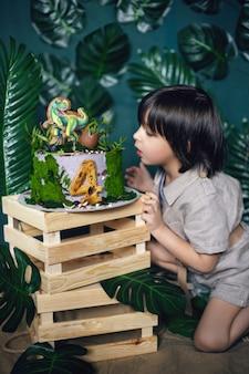 Enfant habillé dans le style d'un chasseur de trésor de la jungle avec un chapeau et un gâteau de dinosaure