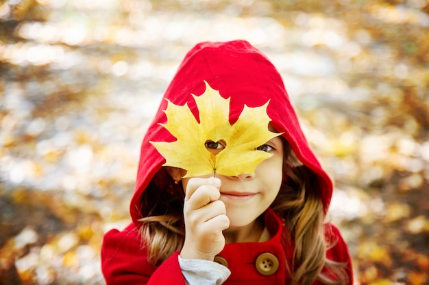 Enfant en habit rouge avec des feuilles d'automne. aime l'automne. mise au point sélective.