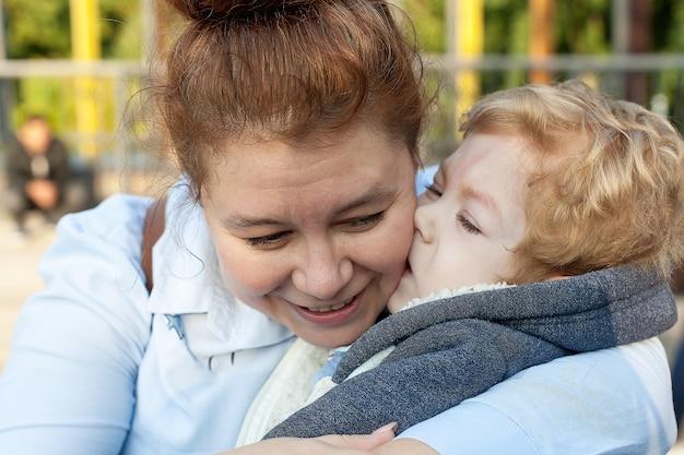 Enfant handicapé embrasse sa mère sur la joue dans le parc lors d'une promenade