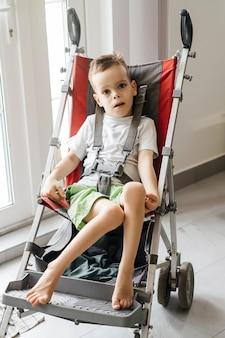 Enfant handicapé en grande poussette accessibilité en fauteuil roulant et poussette