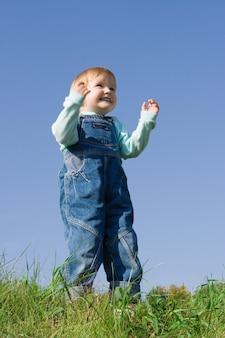 Enfant sur l'herbe verte sous le ciel bleu