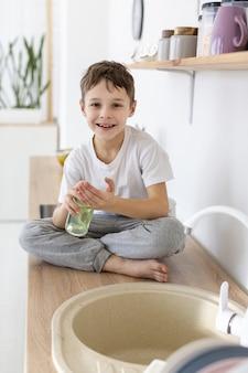 Enfant heureux à l'aide de savon liquide