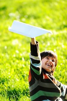 Enfant heureux, appréciant ensoleillé fin d'été et journée d'automne dans la nature sur l'herbe verte