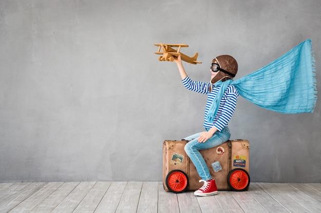 Enfant heureux assis sur une vieille valise habillé comme un pilote avec une cape de super-héros sur fond gris