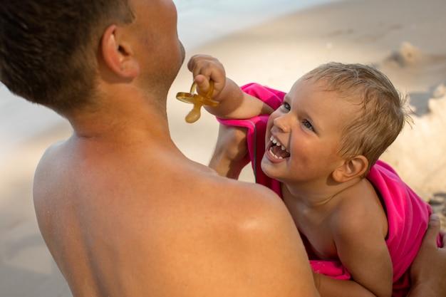 Enfant heureux sur les bras du père de récolte
