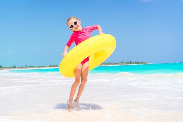 Enfant heureux avec cercle de caoutchouc gonflable s'amuser sur la plage blanche