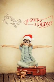Enfant heureux en chapeau de père noël jouant avec un avion jouet à la maison. rétro tonique