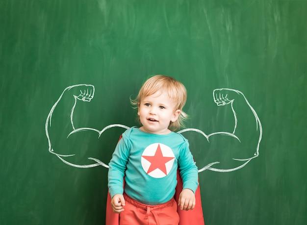 Enfant heureux en classe. enfant drôle contre le tableau. retour à l'école. notion d'éducation