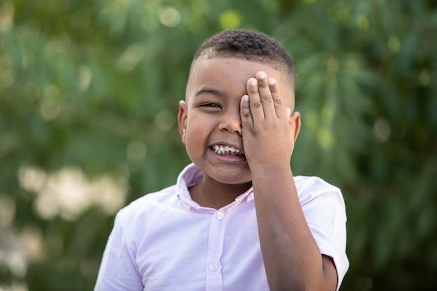 Enfant heureux couvrant son oeil