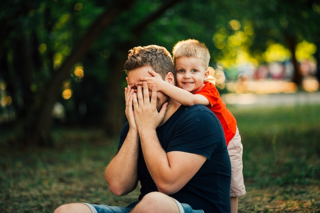 Enfant heureux couvrant les yeux de son père