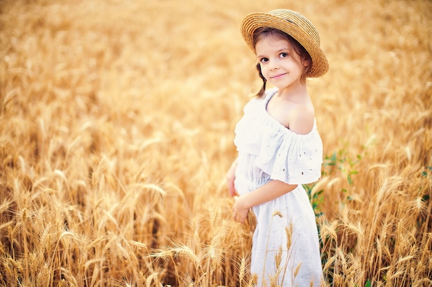 Enfant heureux dans le champ de blé d'automne. belle fille en robe blanche et chapeau de paille s'amuser avec jouer, récolter