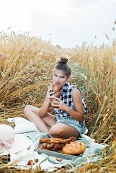 Enfant heureux avec du pain dans le champ de blé d'automne jaune. un champ aux épis matures. une fille est assise sur un couvre-lit, des fruits frais et des baies, du pain et des petits pains dans un panier. pique-nique du village en plein air.