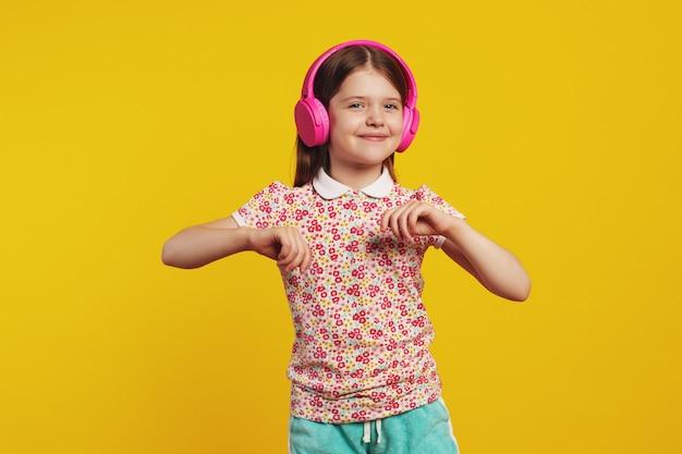 Enfant heureux avec des écouteurs roses écoutant de la musique et dansant contre le jaune