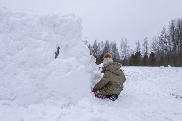 Un enfant heureux fait un bonhomme de neige dans un champ enneigé à la campagne.