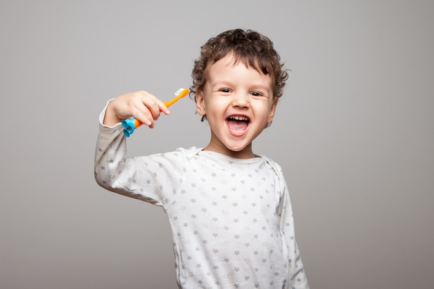 Enfant heureux, garçon, avec une brosse à dents dans les mains, rit et se réjouit. grand sourire ouvert, dents de lait blanches. l'hygiène buccale tous les jours. isolé.