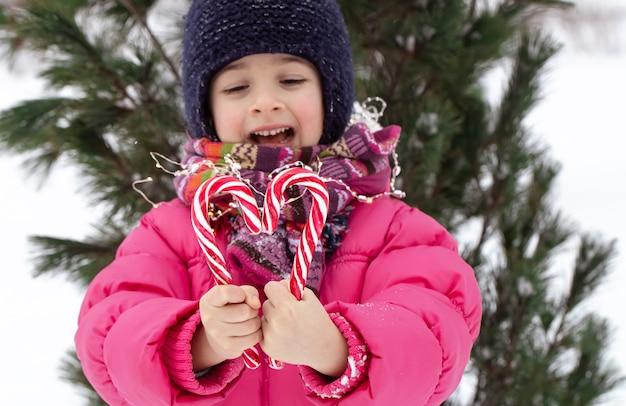 Enfant heureux avec une grosse canne à sucre sous un arbre de noël. concept de vacances d'hiver.