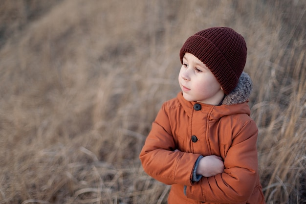 Un enfant heureux joue dans le parc et rêve au grand air en automne.