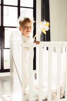Enfant heureux avec jouet dans le berceau