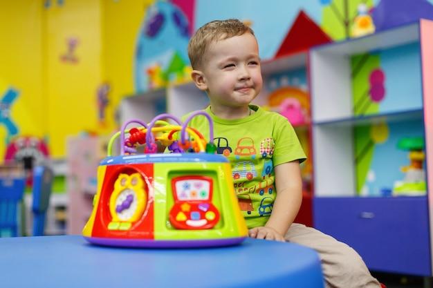 Un enfant heureux avec un jouet intéressant à l'école maternelle et au jardin d'enfants joue avec un jouet coloré