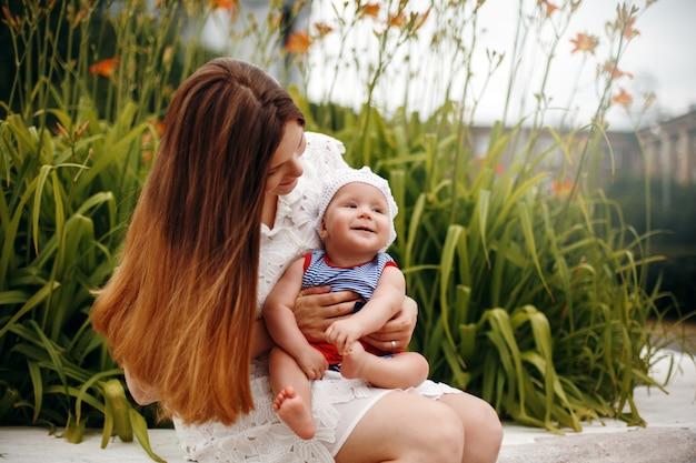 Enfant heureux mignon assis sur les genoux de la mère aimante