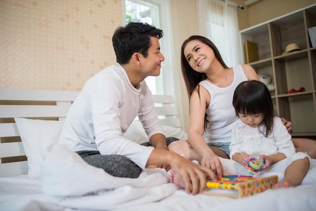 Enfant heureux avec les parents jouant dans le lit à la maison