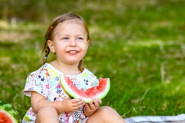 Enfant heureux avec pastèque sur la nature dans le parc