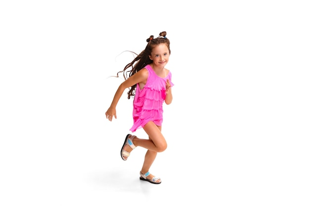Enfant heureux, petite fille caucasienne émotionnelle sautant et courant isolé sur blanc