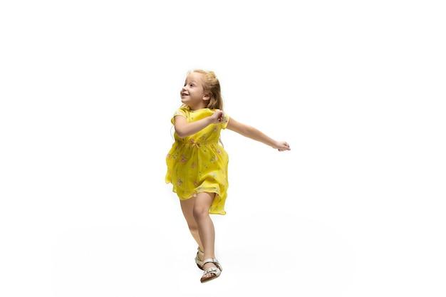 Enfant heureux, petite fille caucasienne émotionnelle sautant et courant isolé sur fond blanc. semble heureux, joyeux, sincère. copyspace pour l'annonce. enfance, éducation, concept de bonheur.