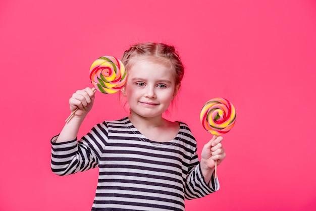 Enfant heureux petite fille avec deux bonbons