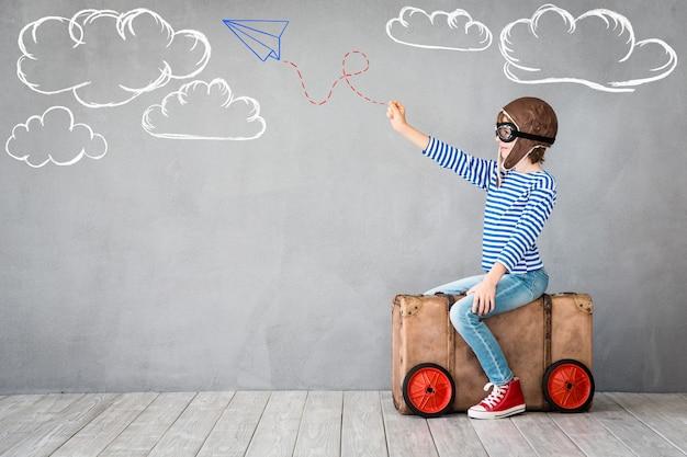 Enfant heureux portant un chapeau de pilote et des lunettes jouant sur fond de mur gris avec des dessins