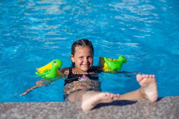L'enfant heureux profite des vacances d'été petite fille charmante dans des brassards gonflables pour nager avec...