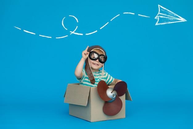Un enfant heureux rêve de devenir pilote contre un mur de papier bleu.