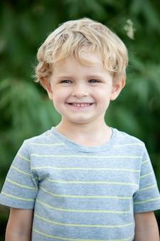 Enfant heureux avec un t-shirt bleu dans le jardin
