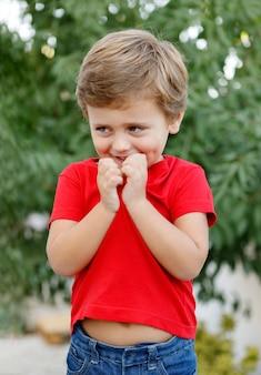 Enfant heureux avec un t-shirt rouge dans le jardin