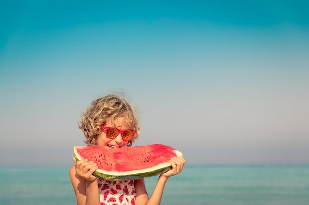 Enfant heureux en vacances d'été enfant mangeant de la pastèque sur la plage concept d'alimentation saine
