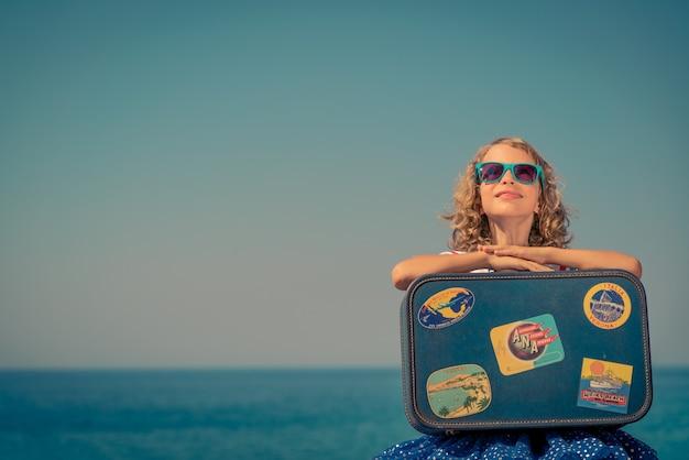 Enfant heureux avec valise sur la plage l'enfant profite de vacances d'été à la mer concept de voyage et de vacances