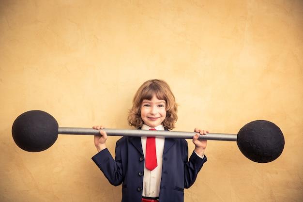 Enfant d'homme d'affaires fort tenant des haltères. concept d'entreprise de succès et de gagnant