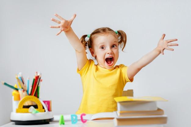 Un enfant impressionné dans la salle de classe avec des crayons et un livre de fournitures scolaires