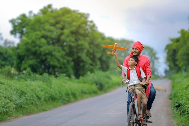 Enfant indien jouant avec avion jouet avec son père en cycle