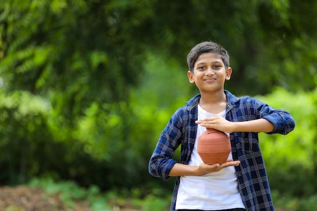 Enfant indien mignon tenant la tirelire d'argile dans la main
