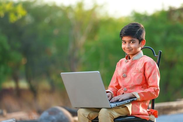 Enfant indien portant un tissu traditionnel et utilisant un ordinateur portable